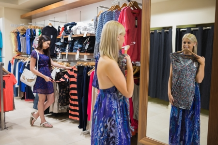 Woman standing in front of mirror holding up shirt in clothing store photo