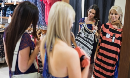 Two women looking in the mirror holding up clothes and smiling Stock Photo - 15592030