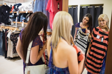 checkout stand: Two women smiling in front of the mirror in clothing store