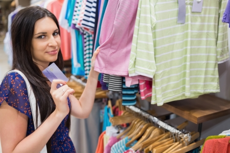 Woman holding credit card beside clothing display in clothes store photo