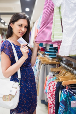 Woman holding clothes showing credit card and smiling photo