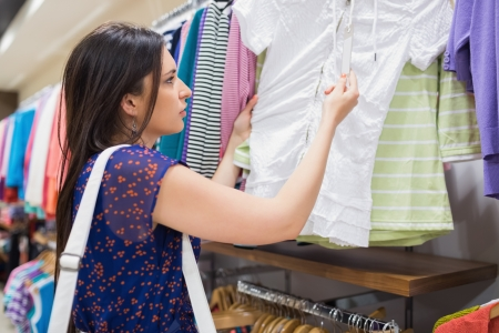 Woman looking at price tag of clothes at the shopping mall photo