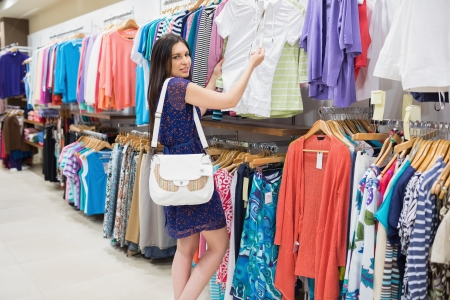 Woman looking at price tag while holding clothes at the shopping mall photo