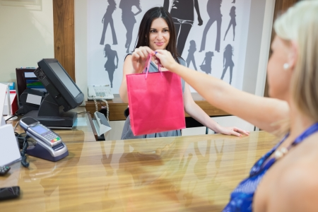 Woman is buying something at cash register in clothing store photo