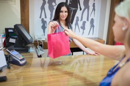 kledingwinkel: Vrouw bij kassa in de kleding winkel