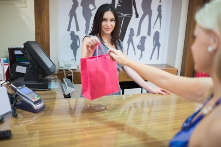 product range: Woman at cash register in clothing store Stock Photo