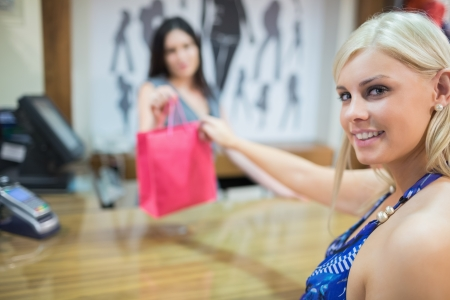 Woman taking purchases at chas register in clothing store photo