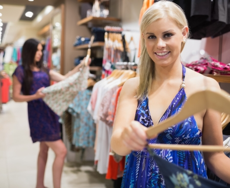 Woman holding dress on hanger and smiling in clothes store photo