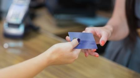 tarjeta de credito: Mujer entrega de tarjeta de cr�dito en la caja registradora Foto de archivo