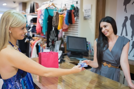 Woman paying with credit card at clothing store photo