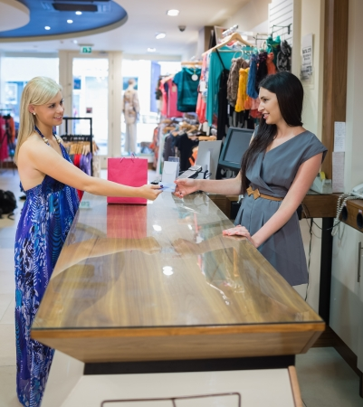 Woman paying with credit card at shopping mall photo