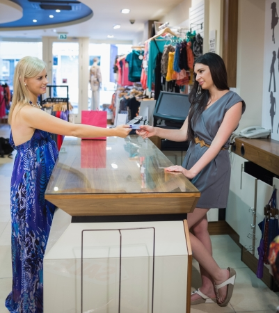 Woman at cash register paying with credit card in clothing store photo