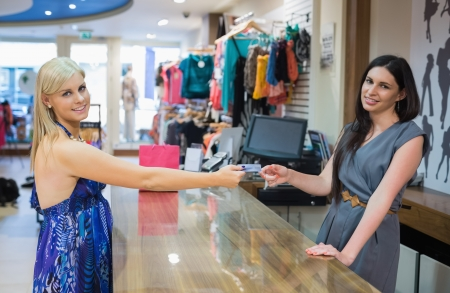 Woman is paying at the counter of the shop Stock Photo - 15591292