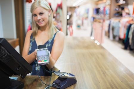 Woman holding credit card mahine in clothing store Stock Photo - 15592555