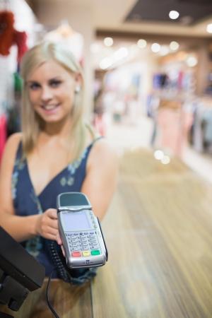automatic transaction machine: Mujer sonriente sosteniendo m�quina de tarjetas de cr�dito en la tienda de ropa