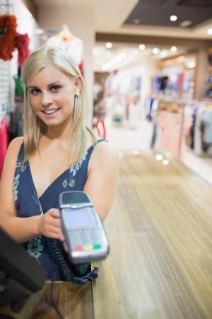 automatic transaction machine: Mujer que muestra la m�quina de tarjetas de cr�dito en la tienda de ropa
