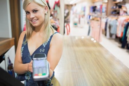 automatic transaction machine: Mujer con la m�quina de tarjetas de cr�dito en tienda de ropa