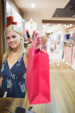 Smiling woman passing shopping bag over counter in clothes store photo