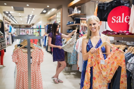 Woman holding up orange shirt in clothing store photo