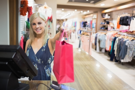 happy shopper: Smiling woman holding shopping bag at counter in clothes store