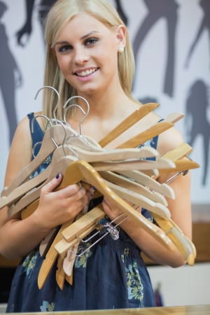 Woman holding hangers and smiling Stock Photo - 15593189