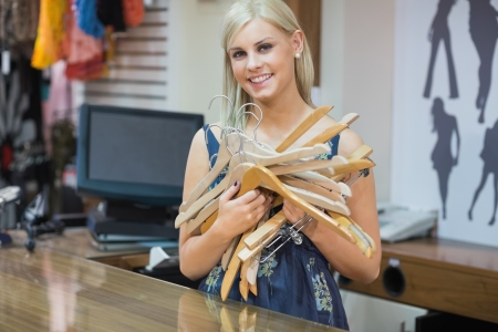 Woma standing behind counter holding hangers in boutique Stock Photo - 15593234