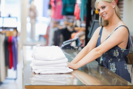 Woman standing behind the counter on the counter with folded clothes photo