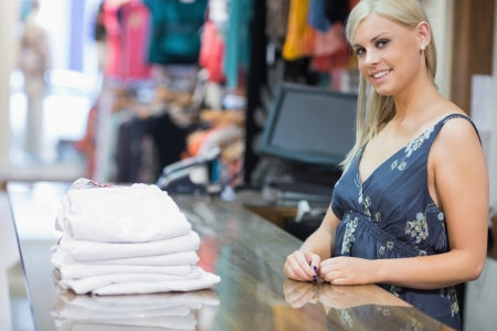 Smiling woman behind counter with folded clothes photo