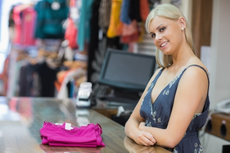 checkout stand: Woman standing behind the counter smiling with clothes folded on the counter