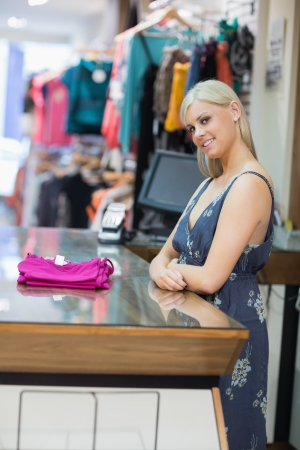 Woman standing at the counter with folded clothes and smiling Stock Photo - 15592705