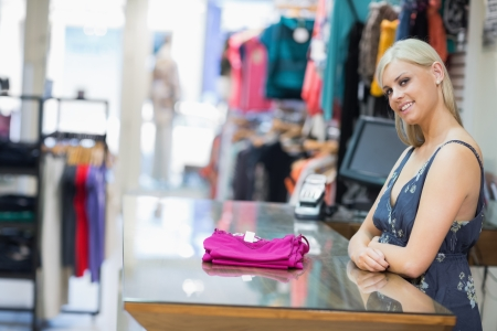 Woman smiling behind counter with folded clothes in clothing store photo