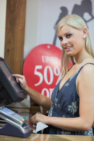 Woman is standing behind counter while typing at the till photo