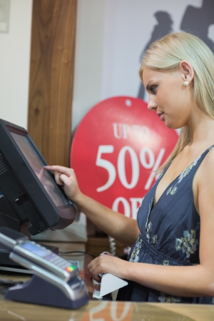 checkout stand: Woman is standing behind the counter of the shop while typing