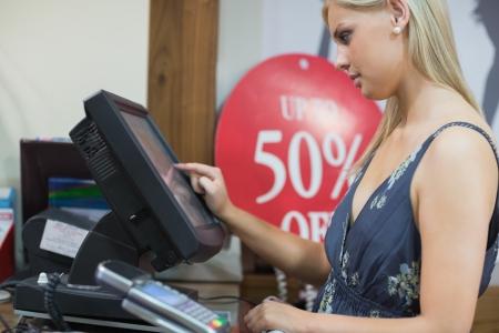 cashpoint: Woman is standing at the counter while typing  Stock Photo