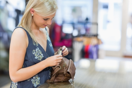 Woman looking in her bag in clothing store photo