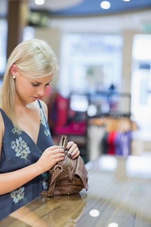 Woman is standing at the counter of the shop while searching in her bag  Stock Photo - 15593011