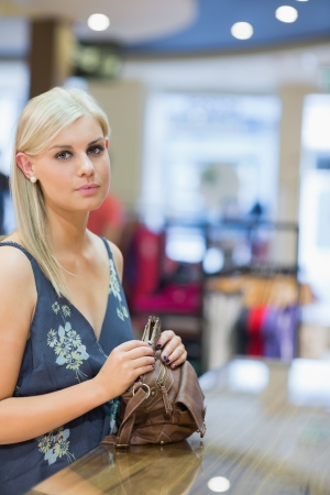 Woman holding handbag at counter in clothing store Stock Photo - 15593088