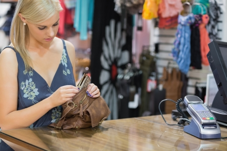 Woman standing at the counter looking through handbag in boutique photo