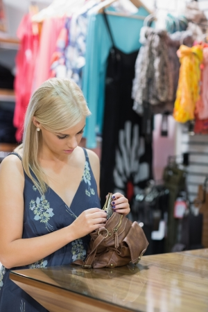 Woman taking purse out of handbag in boutique Stock Photo - 15593430