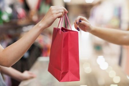 Mujer entrega de bolsa de la compra en la caja registradora Foto de archivo