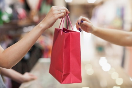 retailer: Woman handing over shopping bag at cash register Stock Photo