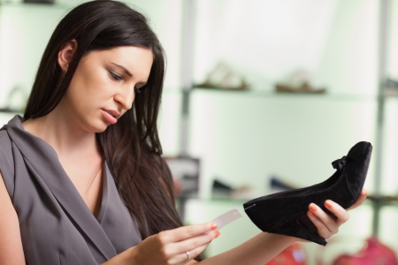 Woman  looking at the price tag of a shoe photo