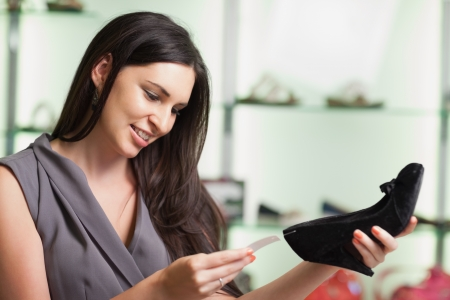 shoe shelf: Woman standing in shop looking at price tag  of shoe and smiling