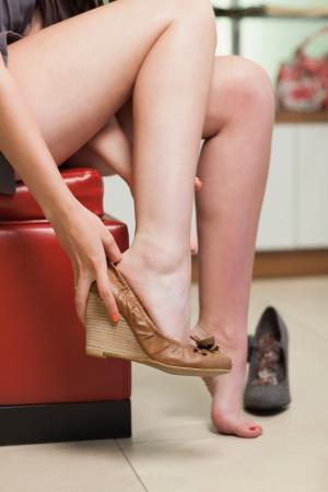 comprando zapatos: La mujer está tratando de zapatos en una tienda
