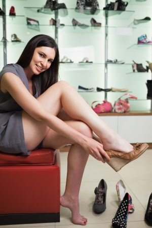 Woman is sitting in a boutique trying shoes and smiling  photo
