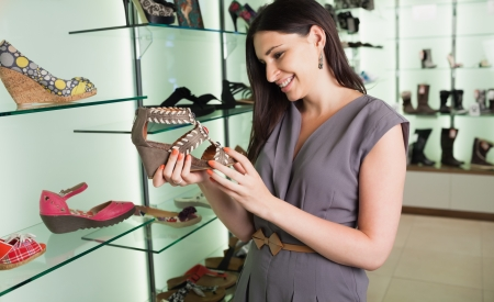 Woman standing in a boutique looking at shoes  photo