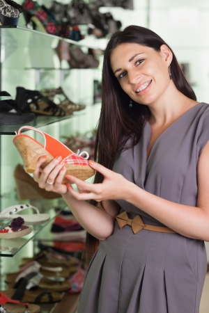 Woman standing in a boutique holding a shoe photo