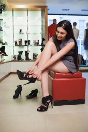 Woman sitting in a boutique trying on shoes  photo