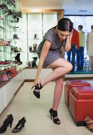 Woman standing in a boutique trying on shoes photo