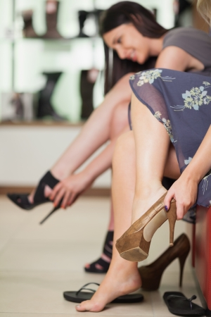 shoe shelf: Two women trying on shoes in a boutique Stock Photo